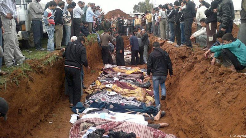 A picture released on April 6, 2012, by the opposition Local Coordination Committees in Syria (LCC) purportedly shows people standing around a mass grave in the town of Taftnaz on April 5, 2012 (AFP Photo/)