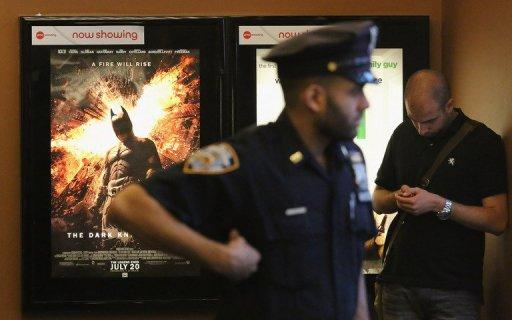 An NYPD officer keeps watch inside a theater where the film 'The Dark Knight Rises' played in Times Square on July 20
