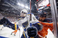 St. Louis Blues' Robert Thomas (18) is checked by Edmonton Oilers' Jason Garrison (13) during the first period of an NHL hockey game, Tuesday, Dec. 18, 2018 in Edmonton, Alberta. (Jason Franson/The Canadian Press via AP)