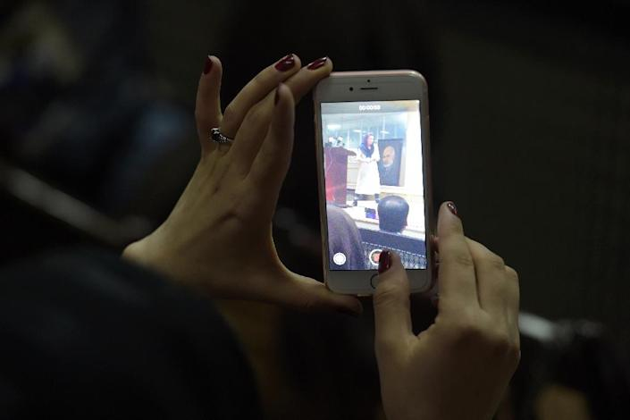 """An Afghan woman records footage on her mobile phone at the first public event for the """"Where Is My Name"""" campaign in Kabul (AFP Photo/Shah MARAI)"""