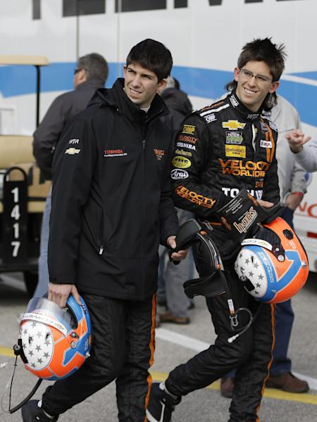 Brothers Ricky Taylor, left, and Jordan Taylor walk through the garage area after a practice session for the IMSA Series Rolex 24 hour auto race at Daytona International Speedway in Daytona Beach, Fla., Thursday, Jan. 23, 2014.(AP Photo/John Raoux)