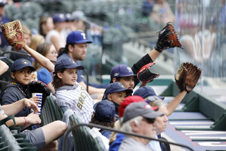 Milwaukee Brewers fans try to get a players attention from behind protective plexi-glass during a preseason baseball game against the Texas Rangers, Tuesday, March 30, 2021, in Arlington, Texas. (AP Photo/Michael Ainsworth)
