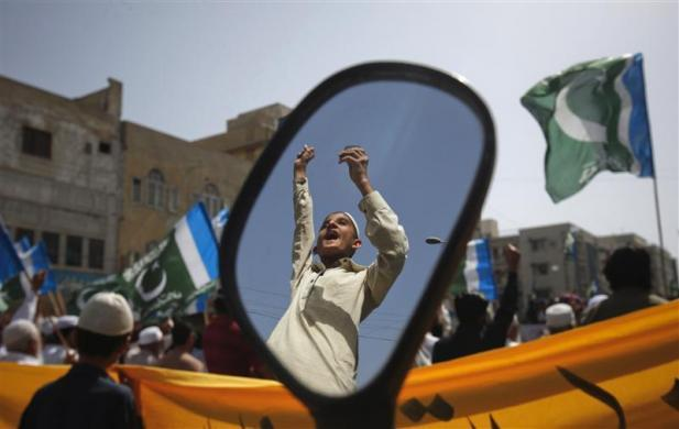 A supporter of the Pakistani religious political party Jamaat-e-Islami is reflected in a mirror of a motorbike during an anti American and NATO demonstration in Karachi March 23, 2012. About 400 protesters gathered to take part in a protest against the possible re-opening of supply routes through Pakistan to NATO troops in Afghanistan, which have been closed since a cross-border attack by NATO forces in Afghanistan that killed 24 Pakistani soldiers on the Pakistan border on November 26, 2011.
