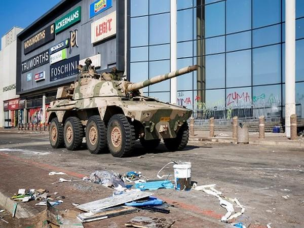 A military tank patrols near a shopping centre that was damaged after several days of looting in Durban, South Africa, July 16, 2021. (Photo Credit: REUTERS)