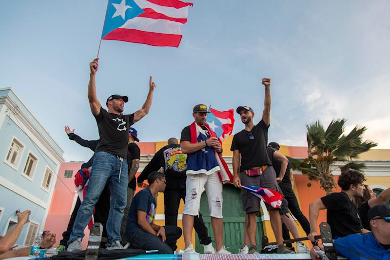 Singer Ricky Martin, left, waves the Puerto Rican flag during march against governor Ricardo Rosello, in San Juan.