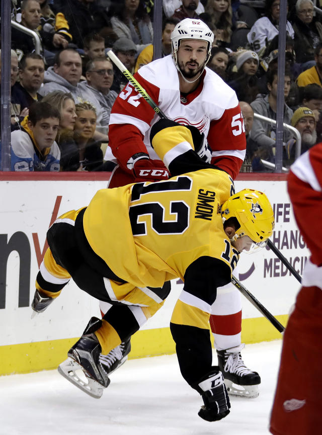 Pittsburgh Penguins' Dominik Simon (12) is hit by Detroit Red Wings' Jonathan Ericsson (52) during the second period of an NHL hockey game in Pittsburgh, Thursday, Dec. 27, 2018. (AP Photo/Gene J. Puskar)