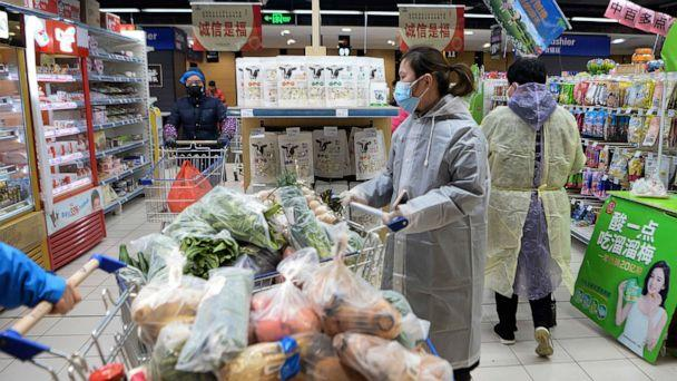 PHOTO: Women wearing protective face masks and raincoats buy foods at a supermarket in Wuhan in central China's Hubei province, Feb. 10, 2020. (Chinatopix via AP)