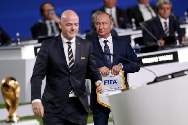Russian President Vladimir Putin, center, attends the FIFA congress with FIFA President Gianni Infantino, left, on the eve of the opener of the 2018 soccer World Cup in Moscow, Russia, Wednesday, June 13, 2018. The congress in Moscow is set to choose the host or hosts for the 2026 World Cup. (AP Photo/Pavel Golovkin)