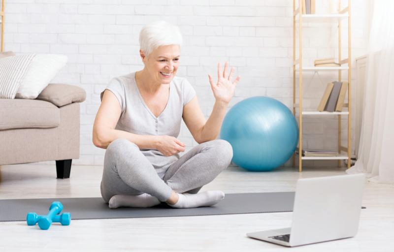 Sporty mature woman showing her training online via laptop, preparing special workout plan for senior people