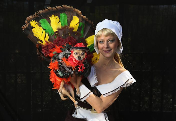 Karen Biehl holds her Chihuahua Eli, who posed as a Thanksgiving turkey at the Tompkins Square Halloween Dog Parade. (Photo by John Moore/Getty Images)