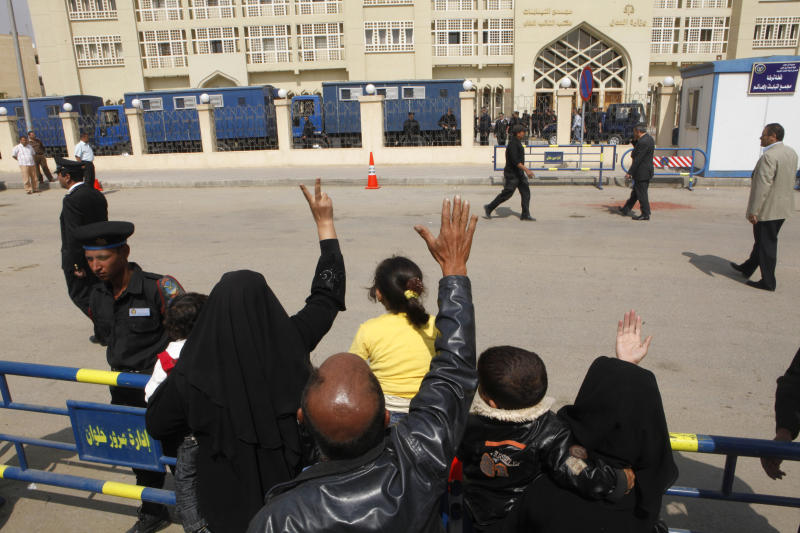 FILE - In this Wednesday, April 28, 2010 file photo, relatives of the 26 suspected Hezbollah members, accused of plotting attacks on tourists and shipping in the Suez Canal and sending operatives and explosives to Gaza to help militant groups there, waves to prison vehicles carrying them outside Emergency State Security Court in New Cairo, Egypt. It was one of the most perplexing events of Egypt's 2011 revolution: Attacks on prisons that broke out more than 20,000 inmates, among them Hamas and Hezbollah militants and Muslim Brotherhood leaders, including the man who is now the country's president, Mohammed Morsi. Now a court case is trying to uncover for the first time who was behind the attacks, raising political headaches for Morsi. (AP Photo/Amr Nabil, File)