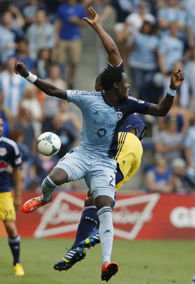 The ball gets past Kansas City Sporting forward Kei Kamara (23) and New York Red Bulls defender Jamison Olave, back, during the first half of an MLS soccer match in Kansas City, Kan., Saturday, Aug. 3, 2013. (AP Photo/Orlin Wagner)