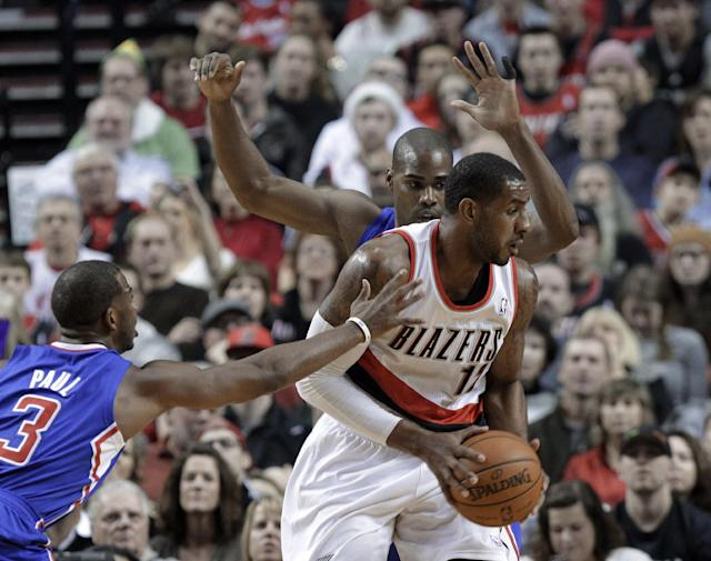 Portland Trail Blazers forward LaMarcus Aldridge, right, is double-teamed by Los Angeles Clippers' Chris Paul, left, and Antawn Jamison during the first half of an NBA basketball game in Portland, Ore., Thursday, Dec. 26, 2013. (AP Photo/Don Ryan)