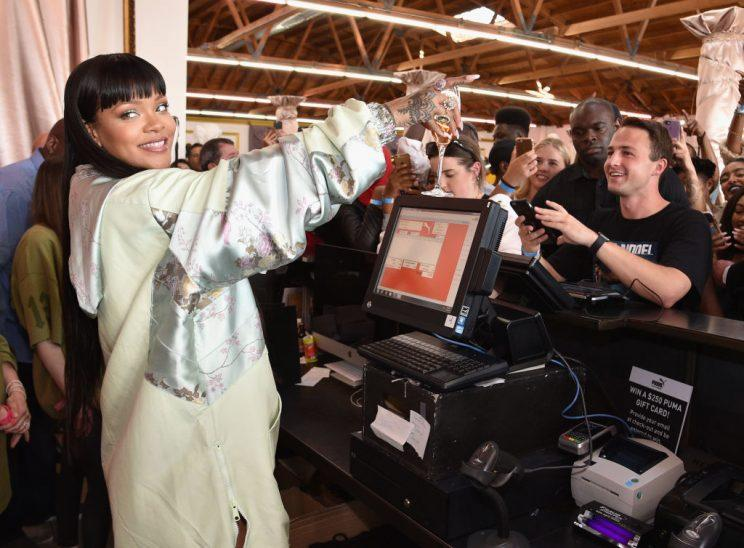 Rihanna, accessorized with a wine glass, worked behind the counter at the Fenty x Puma pop-up shop in L.A. on Tuesday. (Photo: Kevin Mazur/Getty Images for PUMA)