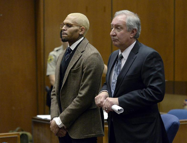 R&B singer Chris Brown, left, appears in court with his attorney Mark Geragos during a probation violation hearing in which his probation was revoked by a superior court judge on Monday, Dec. 16, 2013, in Los Angeles. Superior Court Judge James R. Brandlin revoked Brown's probation after his recent arrest on suspicion of misdemeanor assault in Washington, D.C., but the ruling will not alter the singer's requirements to complete rehab and community labor for his 2009 attack on Rihanna. (AP Photo/Kevork Djansezian, Pool)