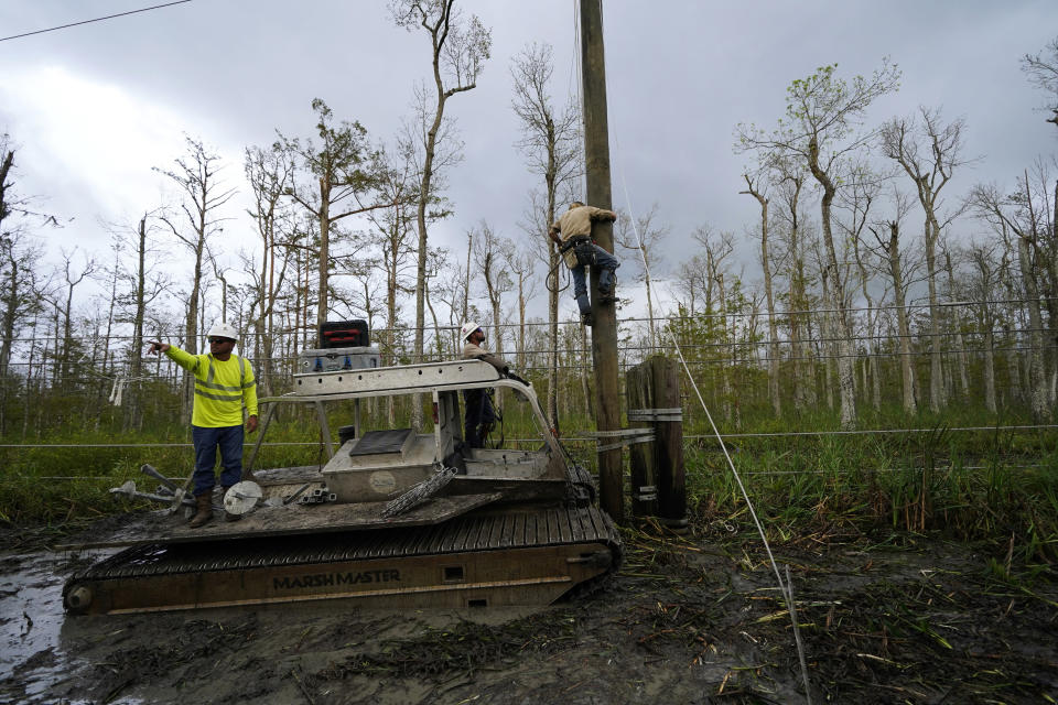Brian Ramshur, an electrical worker for Sparks Energy, climbs a power pole to restore power lines running through a marsh, in the aftermath of Hurricane Ida in Houma, La., Friday, Sept. 17, 2021. The Louisiana terrain presents special challenges. In some areas, lines thread through thick swamps that can be accessed only by air boat or marsh buggy, which looks like a cross between a tank and a pontoon boat. Workers don waders to climb into muddy, chest-high waters home to alligators and water moccasins. (AP Photo/Gerald Herbert)