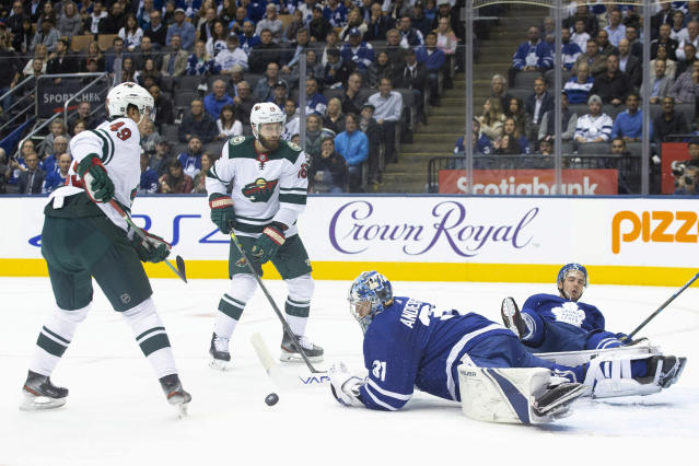 Toronto Maple Leafs goaltender Frederik Andersen sprawls on the ice after stopping the puck in front of Minnesota Wild's Victor Rask (49) and Jason Zucker (16) during the first period of an NHL hockey game Tuesday, Oct. 15, 2019, in Toronto. (Chris Young/The Canadian Press via AP)
