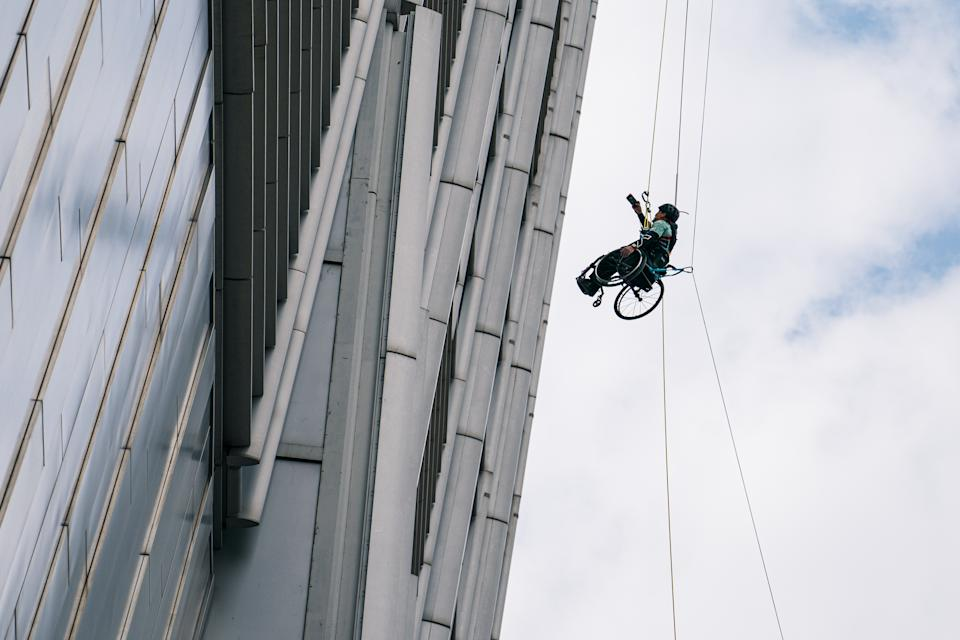 HONG KONG, CHINA - JANUARY 16: (EDITORIAL USE ONLY) Wheelchair Climber Lai Chi-wai taking selfies with the public when he completes 250-meter (75/f) out of 320-meter during his attempt to climb the 89-storey Nina Tower in Tsuen Wan by using only his upper body strength. The challenge raised over HK$5 million for spinal cord patients to utilize exoskeletons on January 16, 2021 at Nina Tower skyscraper, in Tsuen Wan, Hong Kong, China. (Photo by Lampson Yip - Clicks Images/Getty Images)