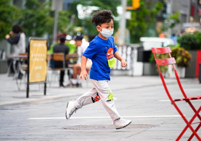 NEW YORK, NEW YORK - AUGUST 16: A kid wears a protective face mask in Times Square as the city continues Phase 4 of re-opening following restrictions imposed to slow the spread of coronavirus on August 16, 2020 in New York City. The fourth phase allows outdoor arts and entertainment, sporting events without fans and media production. (Photo by Noam Galai/Getty Images)