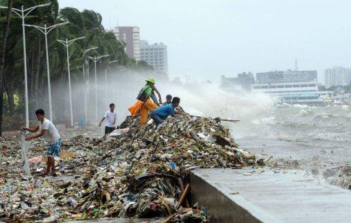 People collect recyclable material from rubbish washed ashore on Roxas boulevard promenade in Manila on August 1, 2012. The National Disaster Risk Reduction and Management Council in Manila said nine more people were killed due to drowning and other accidents related to Typhoon Saola, raising the toll to 23 overnight