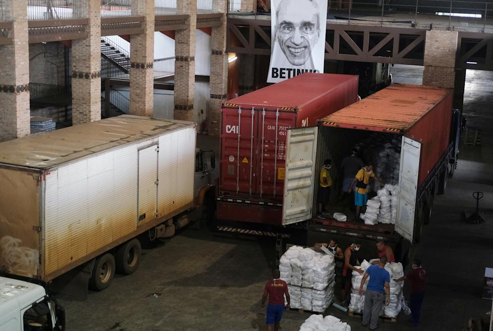 Workers unload trucks with aid donations at the warehouse of NGO Acao e Cidadania, during the coronavirus disease (COVID-19) outbreak, on the outskirts of Rio de Janeiro, Brazil April 17, 2020. Picture taken April 17, 2020. REUTERS/Ricardo Moraes