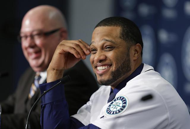 Robinson Cano, right, smiles as he sits next to Seattle Mariners general manager Jack Zduriencik, left, after Cano was introduced as the newest member of the Seattle Mariners baseball team, Thursday, Dec. 12, 2013, in Seattle. (AP Photo/Ted S. Warren)