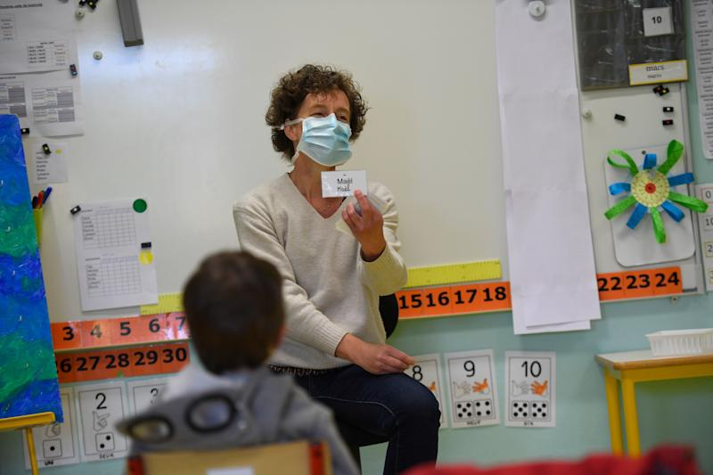 A teacher wearing a protective mask teaches children in her classroom at Champ l'Eveque public school in Bruz, western France, on May 12, 2020, after France eased lockdown measures taken to curb the spread of the COVID-19 pandemic, caused by the novel coronavirus. (Photo by Damien MEYER / AFP) (Photo by DAMIEN MEYER/AFP via Getty Images)