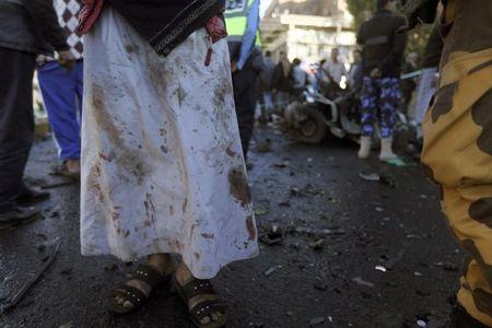 A medic with blood on his clothes stands at the scene of a car bomb attack outside the police college in Sanaa