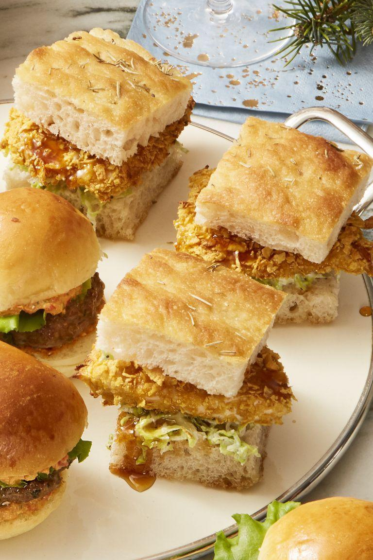 """<p>Smothered with corn flakes and buttermilk, these crispy roasted chicken sliders will bring your party guests good tidings of comfort <em>and</em> joy. </p><p><a class=""""link rapid-noclick-resp"""" href=""""https://www.amazon.com/Mikes-Hot-Honey-12-oz/dp/B011LWRBES?tag=syn-yahoo-20&ascsubtag=%5Bartid%7C10055.g.794%5Bsrc%7Cyahoo-us"""" rel=""""nofollow noopener"""" target=""""_blank"""" data-ylk=""""slk:SHOP HOT HONEY"""">SHOP HOT HONEY</a></p><p><em><a href=""""https://www.goodhousekeeping.com/food-recipes/party-ideas/a25310452/crispy-hot-honey-chicken-sliders-recipe/"""" rel=""""nofollow noopener"""" target=""""_blank"""" data-ylk=""""slk:Get the recipe for Crispy Hot-Honey Chicken Sliders »"""" class=""""link rapid-noclick-resp"""">Get the recipe for Crispy Hot-Honey Chicken Sliders » </a></em></p>"""