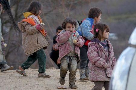 Internally displaced children, covered with mud, wait with their families as they are stuck in the town of Khirbet Al-Joz, in Latakia countryside, waiting to get permission to cross into Turkey near the Syrian-Turkish border, Syria, February 7, 2016. REUTERS/Ammar Abdullah