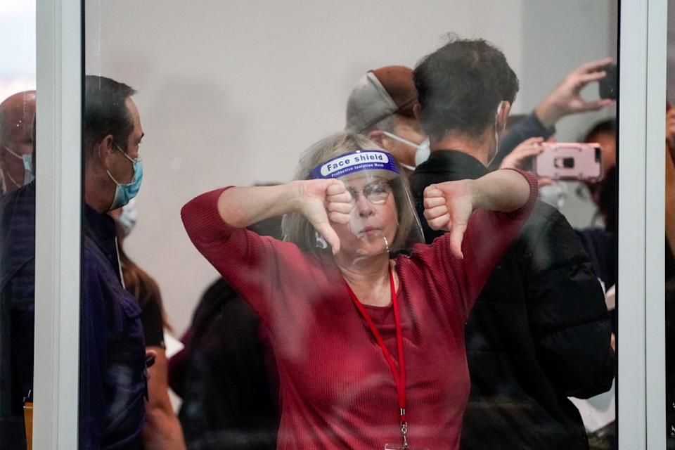 A woman wearing a face shield gives the thumbs down.