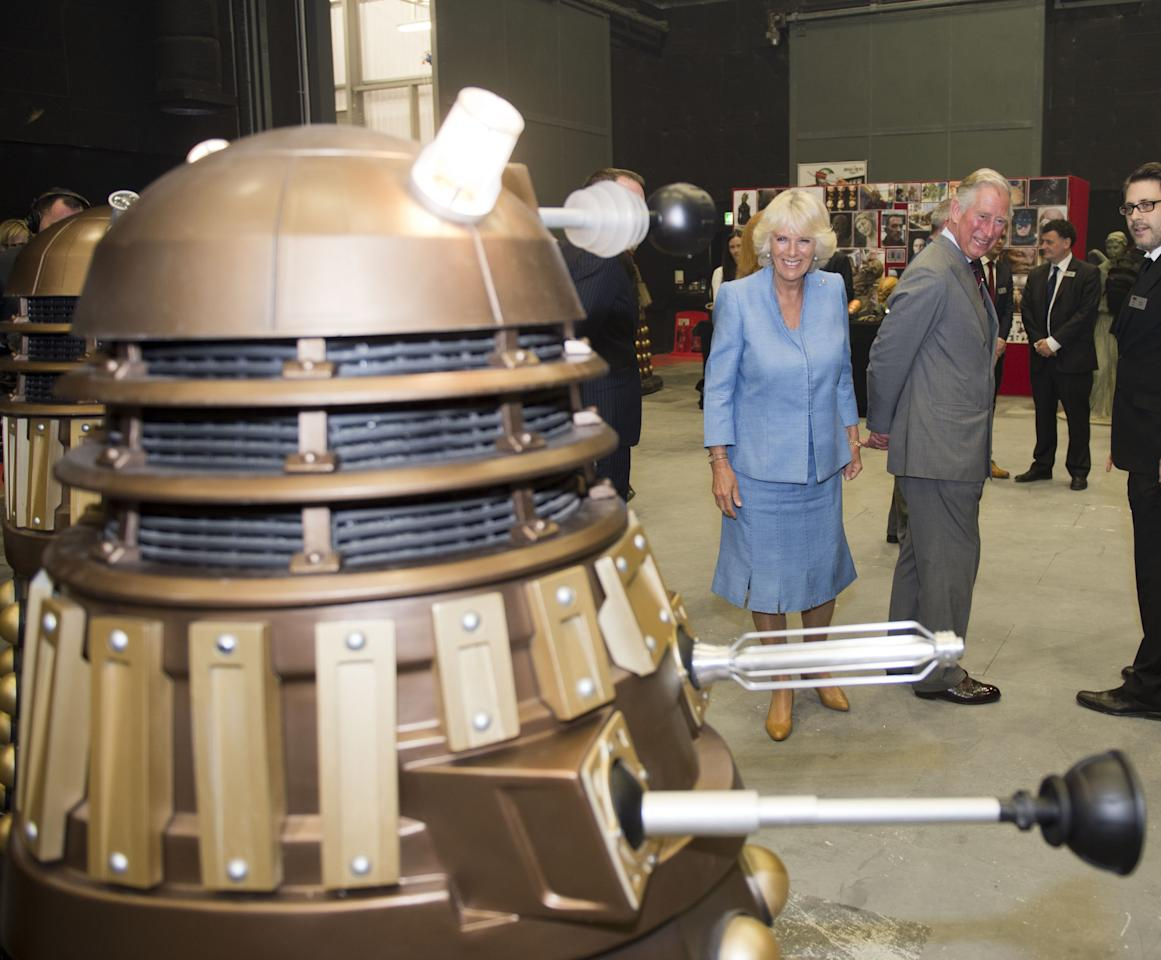 CARDIFF, WALES - JULY 03: Camilla, Duchess of Cornwall and Prince Charles, Prince of Wales are seen looking at Daleks during their visit to the set of the BBC One drama series 'Doctor Who' during their visit BBC Roath Lock Studios on July 3, 2013 in Cardiff, Wales. (Photo by Arthur Edwards - WPA Pool/Getty Images)