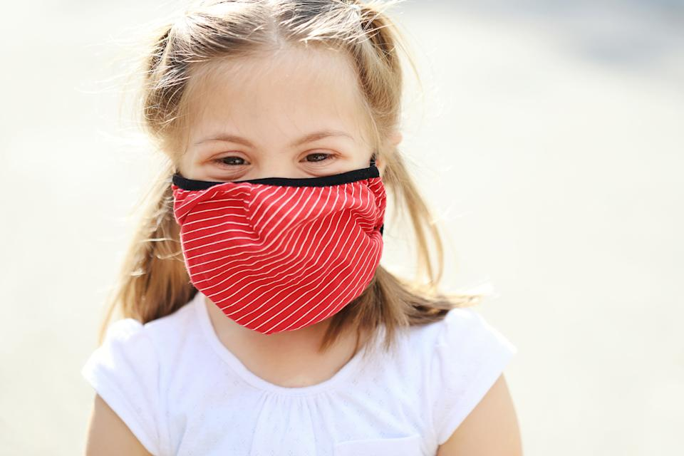 Cheerful little girl with down syndrome wearing face protective mask
