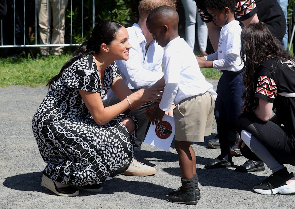 CAPE TOWN, SOUTH AFRICA - SEPTEMBER 23: Meghan, Duchess of Sussex and Prince Harry, Duke of Sussex meet young wellwishers as they visit a Justice Desk initiative in Nyanga township, during their royal tour of South Africa on September 23, 2019 in Cape Town, South Africa. The Justice Desk initiative teaches children about their rights and provides self-defence classes and female empowerment training to young girls in the community. (Photo by Chris Jackson/Getty Images)