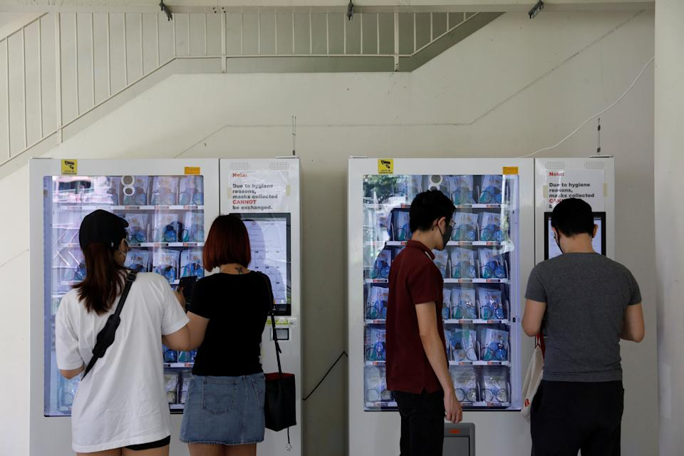 Residents collect free protective face masks from vending machines in their housing estate.