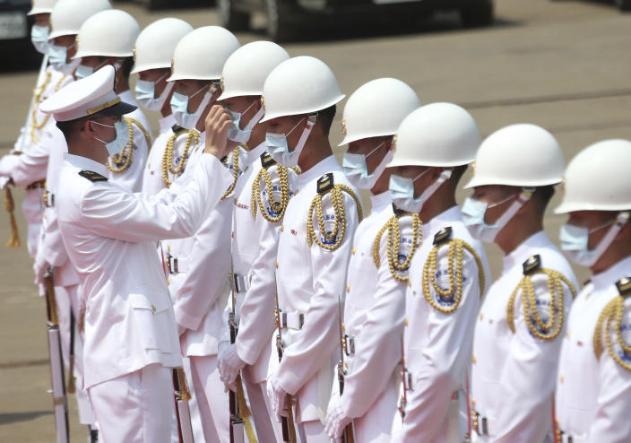 A Taiwan Navy honor guard captain adjusts team member's face mask during a launch ceremony for its first indigenous amphibious transport dock in Kaohsiung, southern Taiwan, Tuesday, April 13, 2021. (AP Photo/Chiang Ying-ying)