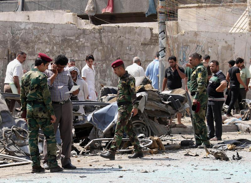 Security forces and citizens inspect the site of a car bomb attack in front of the Ministry of Higher Education and Scientific Research in central Baghdad, Iraq, Wednesday, Sept. 18, 2013. An Iraqi police officer said a parked car bomb exploded in a deadly attack on a commercial area in central Baghdad. More than 4,000 people have been killed since April, including over 804 just in August, according to U.N. figures. (AP Photo/ Hadi Mizban)