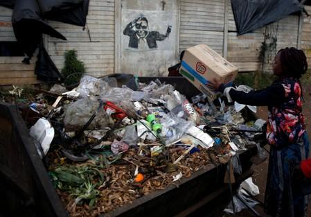 A woman dumps garbage in a bin besides a mural of late former Zimbabwe's President Robert Mugabe, in Mbare township, Harare