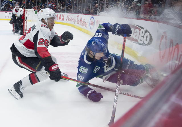 Ottawa Senators defenseman Erik Brannstrom (26) goes into the boards with Vancouver Canucks center Adam Gaudette (88) during the second period of an NHL hockey game Tuesday, Dec. 3, 2019, in Vancouver, British Columbia. (Jonathan Hayward/The Canadian Press via AP)