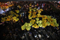 Inflatable yellow ducks, which have become good-humored symbols of resistance during anti-government rallies, are lifted over a crowd of protesters Friday, Nov. 27, 2020 in Bangkok, Thailand. Pro-democracy demonstrators are continuing their protests calling for the government to step down and reforms to the constitution and the monarchy, despite legal charges being filed against them and the possibility of violence from their opponents or a military crackdown. (AP Photo/Sakchai Lalit)