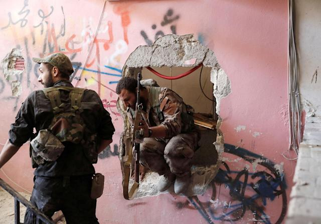 <p>Members of the Syrian Democratic Forces pass through a hole in the wall as they advance their positions towards the Islamic State militants who are holed up at a stadium in Raqqa, Syria, Oct. 4, 2017. (Photo: Erik De Castro/Reuters) </p>