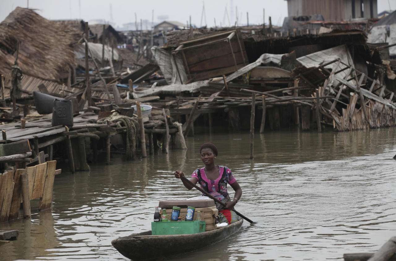 In this photo taken Thursday, July 26, 2012, a woman paddles a canoe past demolished stilts houses at Makoko in Lagos, Nigeria. The teeming, floating Makoko slum rises out of the murky lagoon water that separates mainland Nigeria from the island that gave birth to its largest city, a permanent haze of smoke rising from its homes built on timber stilts. A government-led eviction last week that saw men in speedboats destroy homes with machetes there left about 3,000 people homeless and raised new fears among activists that authorities may try to wipe it out the area entirely. (AP Photo/Sunday Alamba)