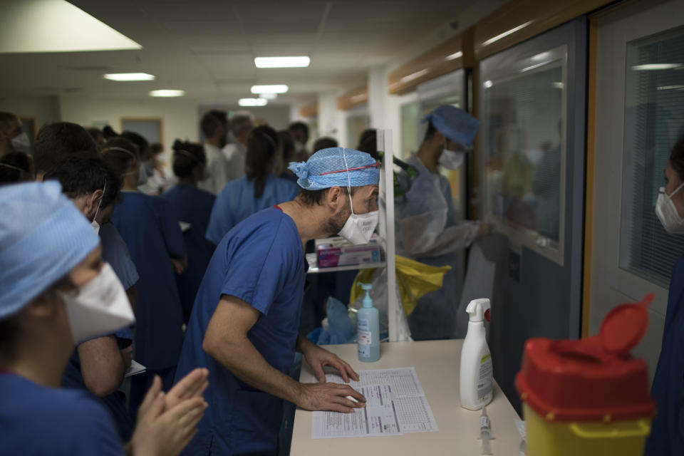 A medical worker peers through the glass of an ICU room containing a COVID-19 patient at the La Timone hospital in Marseille, southern France, Thursday, Nov. 12, 2020. (AP Photo/Daniel Cole)