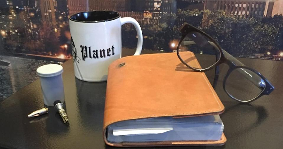 <p>No good reporter would be without notebook, glasses, and coffee mug.</p>