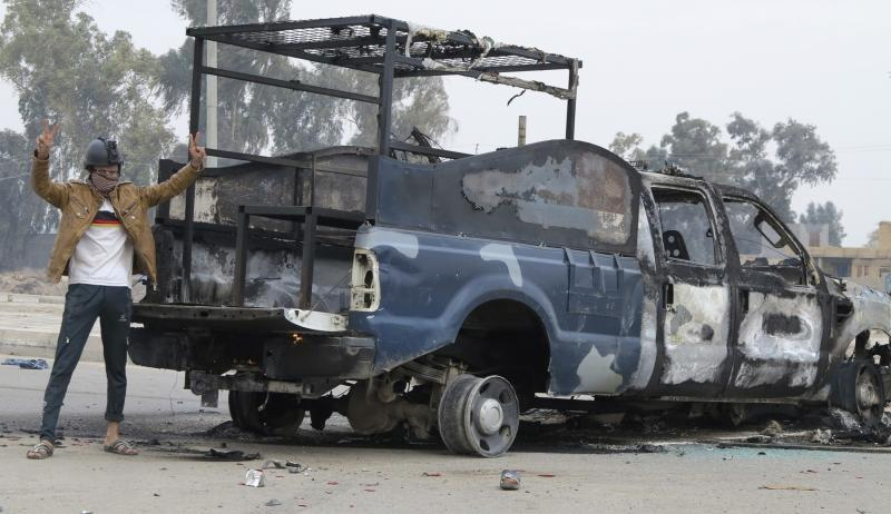 A protester stands next to the wreckage of a police vehicle in Ramadi