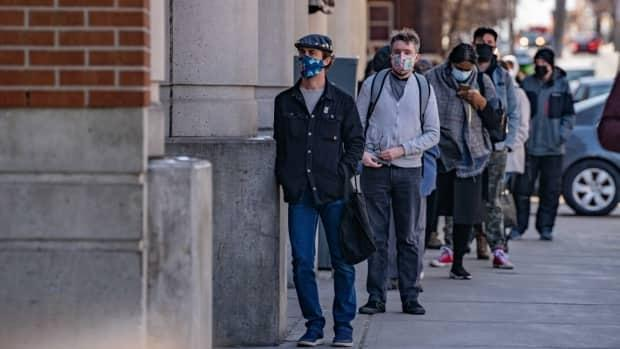 People wearing masks line up outside a business in Ottawa. (Mathieu Theriault/CBC - image credit)