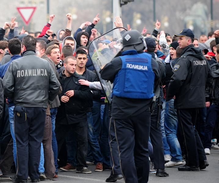 A group of ethnic Albanians confront the police during a protest through a street in Skopje, Macedonia, on Saturday, March 2, 2013, as they show their support for newly named defence minister Talat Xhaferi, and as a contra-protest to Macedonian protests overnight Friday when scuffles broke out with police. A series of scuffles erupted late on Friday and continued over night when a group of a few hundred Macedonians started protesting against the designation of the new defense minister Talat Xhaferi, an ethnic Albanian and former rebel commander. (AP Photo/Vangel Tanurovski)