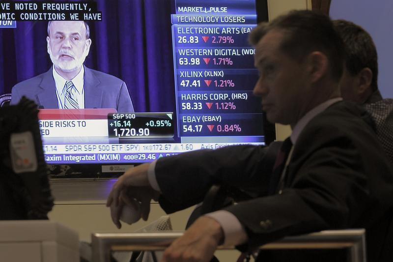 A trader watches U.S. Federal Reserve Board Chairman Ben Bernanke's news conference on the floor of the New York Stock Exchange,