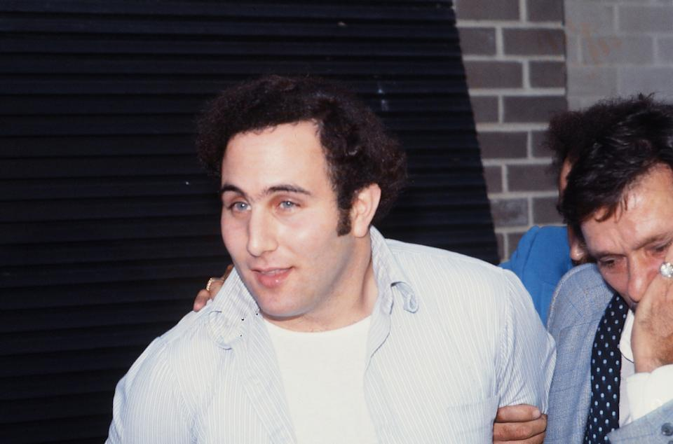 Police officers escort American accused (and ultimately convicted) serial killer David Berkowitz (left), known as the Son of Sam, into the 84th precinct station, New York, New York, August 10, 1977. (Photo by Robert R. McElroy/Getty Images)