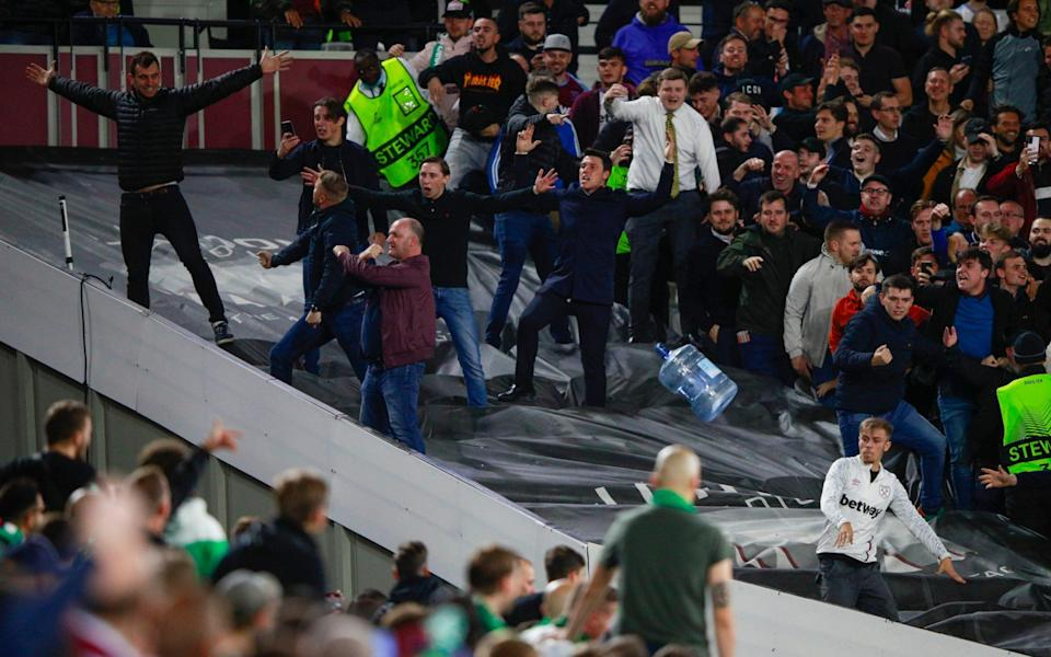 A water bottle is thrown at visiting fans during the Europa League Group H soccer match between West Ham and Rapid Vienna - AP
